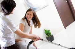 Beautiful girl with vacuum cleaner and boy Royalty Free Stock Photos