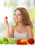 Beautiful girl with vegetables in the kitchen. Beautiful young woman with vegetables in the kitchen royalty free stock photography
