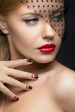 Beautiful girl with a veil, evening makeup, black. And red nails. Design manicure. Beauty face. Picture taken in the studio Royalty Free Stock Photography