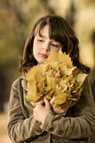 Beautiful girl. Vertical photo, beautiful sorrow little girl hold many yellow leaf, autumnal portrait stock photo
