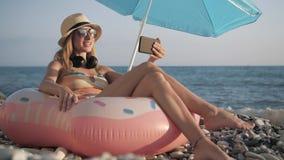 Beautiful girl video chats on smart phone on beach