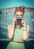 Beautiful girl in vintage clothing making picture with retro cam Stock Image