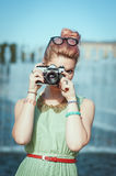 Beautiful girl in vintage clothing making picture with retro cam Stock Photos