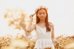 Beautiful girl in vintage dress and hat standing near colorful flowers stock images