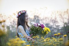 Beautiful girl in vintage dress and hat standing near colorful flowers stock photos