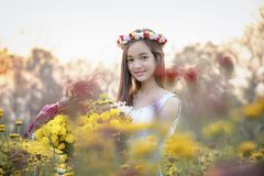 Beautiful girl in vintage dress and hat standing near colorful flowers stock image
