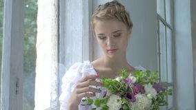 Beautiful girl in vintage white dress sitting on stock video footage