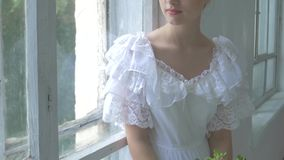 Beautiful girl in vintage white dress sitting on stock footage