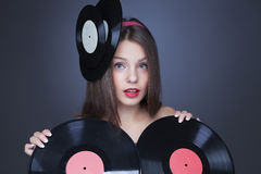 Beautiful girl with vinyl disc on black background Stock Photos