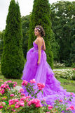 Beautiful girl in violet dress among in the garden Royalty Free Stock Photos