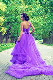 Beautiful girl in violet dress among in the garden Stock Photography