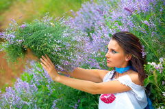 Beautiful girl between violet flowers Stock Photography
