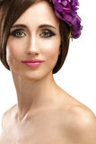 Beautiful girl with violet flowers in her hair beauty shot Royalty Free Stock Image