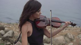 Beautiful girl with violin. Young violinist in dress plays at sea background stock video footage