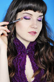 Beautiful girl visagiste with tassel for make-up with long hair Stock Photo