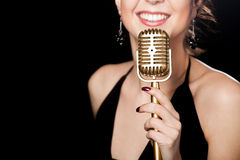 Beautiful girl vocalist with smile holding golden vintage microphone. Elegant young female singer in black dress smiling holding golden vintage microphone, live stock photo