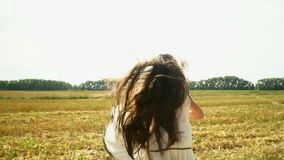 The beautiful girl in a volume dress runs across the field. Sunny day. The slanted field of wheat in Russia. Cute little. On this video you can see as the girl stock video footage