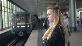 Beautiful girl waiting for a subway train. Subway train drives up to station. Beautiful girl waiting for a subway train. Attractive young woman stands at station stock footage