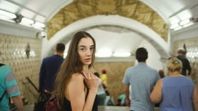 Beautiful girl walk through underpass crowd many people turn to camera look.
