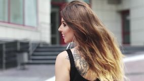 Beautiful girl walking around the city and listening to music on headphones with the mobile phone. young woman dancing stock video footage