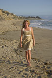 Beautiful Girl walking on the Beach in dress Stock Image