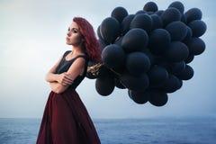 Beautiful girl walking with black balloons Royalty Free Stock Image