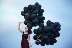 Beautiful girl walking with black balloons Royalty Free Stock Photos
