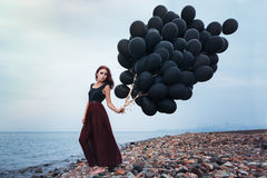 Beautiful girl walking with black balloons Stock Photo