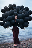Beautiful girl walking with black balloons Stock Photos