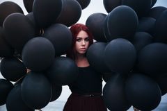Beautiful girl walking with black balloons Stock Photography