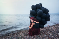 Beautiful girl walking with black balloons Royalty Free Stock Images
