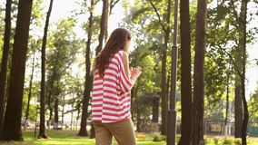 Beautiful girl is walking in city park and using smartphone, young woman is holding device and touching screen, summer. Nature is visible stock video footage