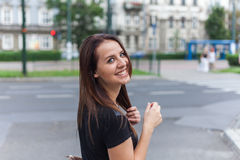 Beautiful girl walking on the city street with happy smile. Royalty Free Stock Photography