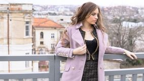 Beautiful girl walking in the coats on the street. 1 stock video