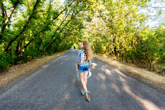Beautiful girl walking on an empty road between green trees. Beautiful girl in blue plaid shirt walking on an empty road between green trees Stock Photography