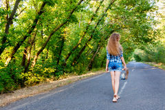 Beautiful girl walking on empty road between green trees. Beautiful girl in blue plaid shirt walking on an empty road between green trees Royalty Free Stock Photo