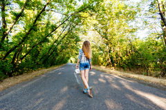 Beautiful girl walking on an empty road between green trees Stock Photos