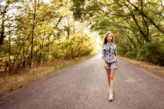 Beautiful girl walking on empty road between green trees Royalty Free Stock Photography