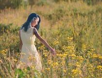 Beautiful girl walking on flower field Stock Image