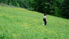 Beautiful girl walking on the green flowery lawn. Clear summer day. Forest in the background. Slow motion.  stock video
