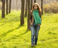 Beautiful girl walking at green grass at park. Royalty Free Stock Photography