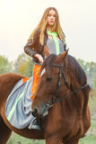 A beautiful girl is walking her horse. Focus on the girl. The warm tone of the image. Soft focus. Stock Photos