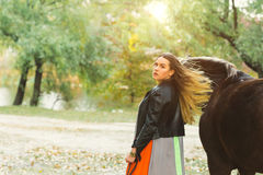 A beautiful girl is walking her horse. Focus on the girl. The warm tone of the image. Soft focus. Stock Images