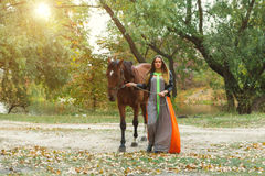 A beautiful girl is walking her horse. Focus on the girl. The warm tone of the image. Soft focus. Stock Photography