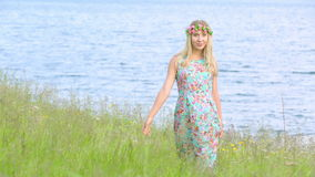Beautiful girl walking in meadow wearing floral wreath. Young adult. Wearing stylish dress with flower print. stock footage