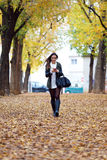 Beautiful girl walking with mobile phone in autumn. Stock Photo