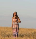 The beautiful girl is walking in oat field. Stock Photos
