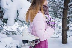 Beautiful girl walking with pair of skates Royalty Free Stock Image