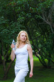 Beautiful girl walking in park and drinking water Royalty Free Stock Photography