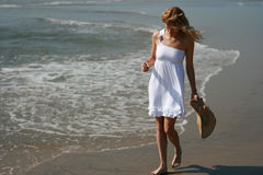 Beautiful girl walking past waves Royalty Free Stock Photo